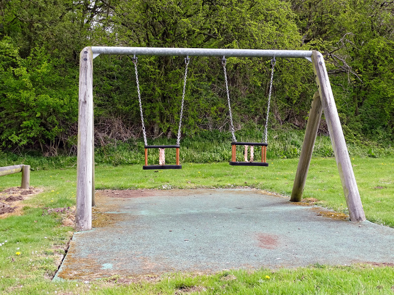 Toddler swings in children's play area in Powburn