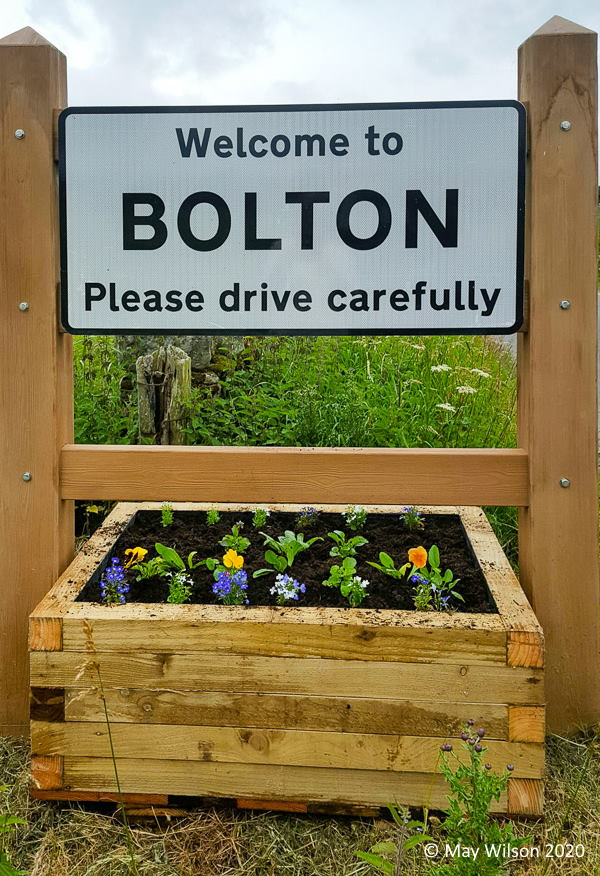 Road sign planter at Bolton Village with plants in place