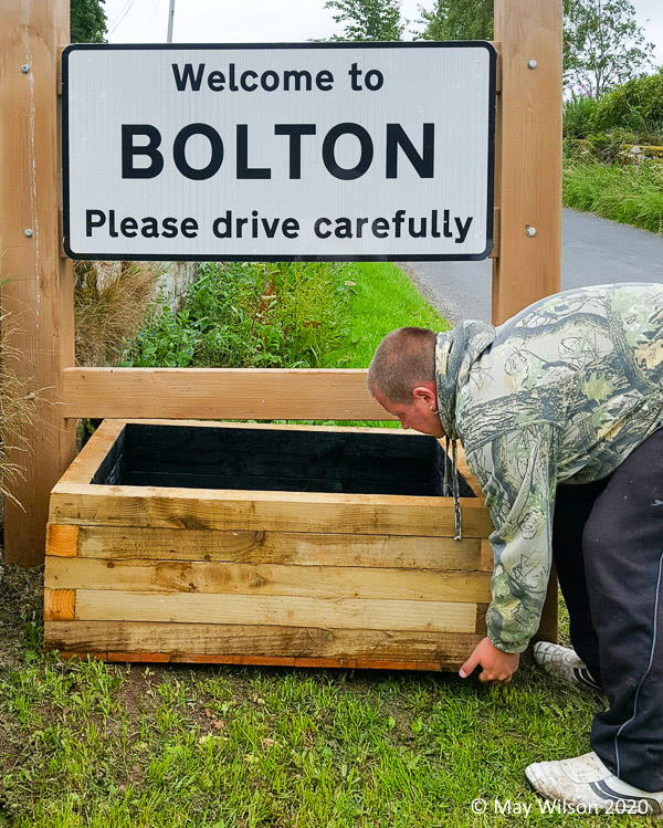 Chris Armit installing road sign planter at Bolton Village