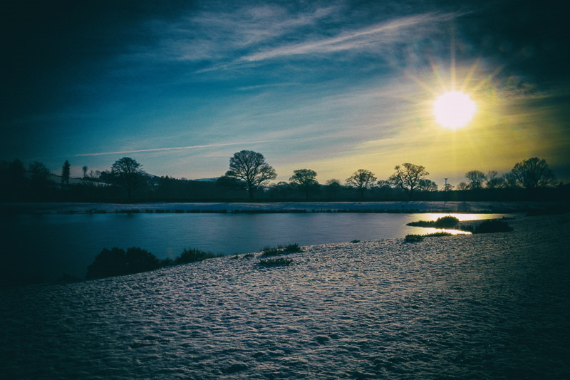 Photo of low sun shining over a partially frozen lake