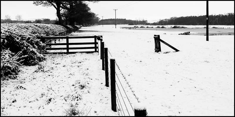 Photo of wooden fence in snow covered field