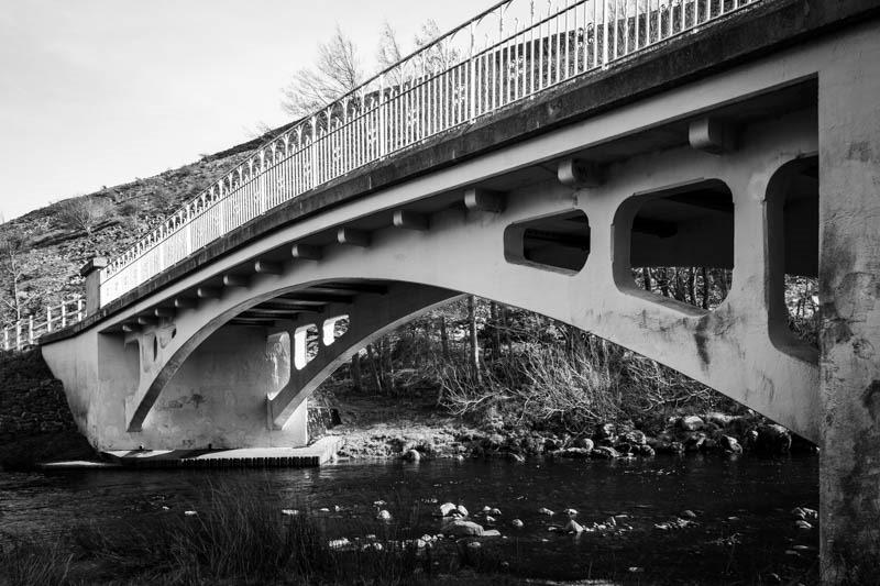 Black and white photo of a bridge over a river