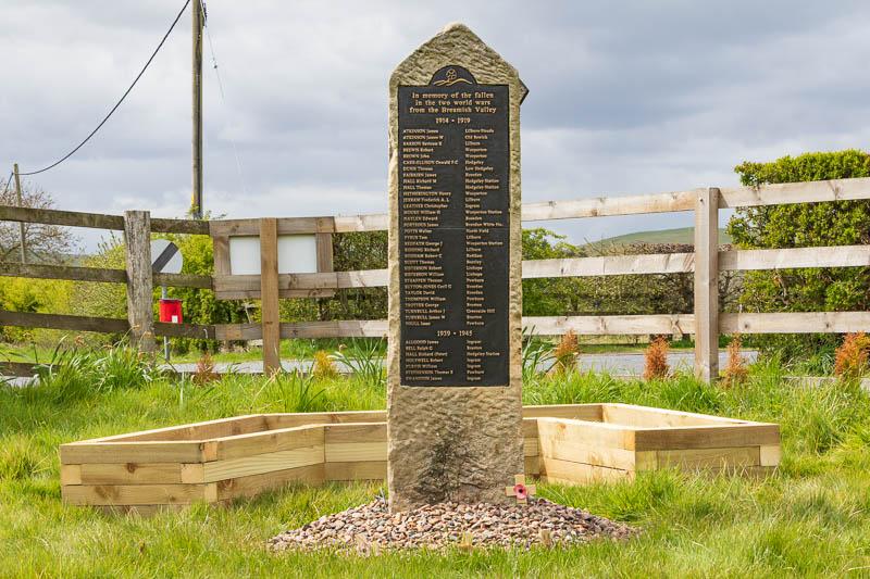 Photo of war memorial in front of wooden planter