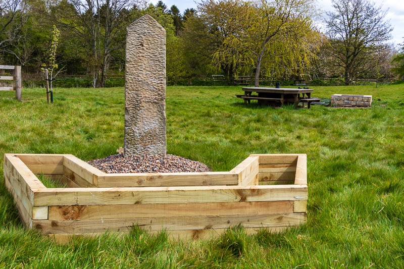 Photo of wooden planter behind war memorial