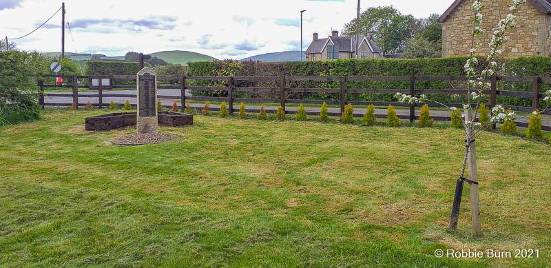 Landscape photo of garden showing war memorial and planter
