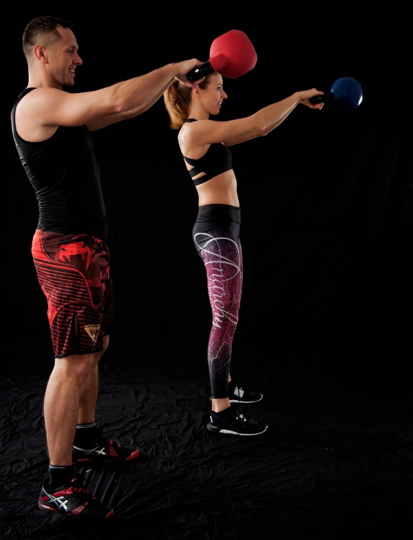Photo of man and woman standing while exercising with kettlebells