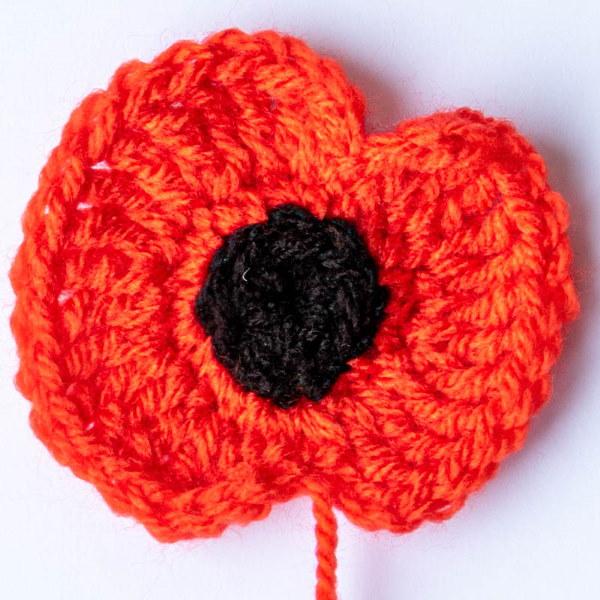 Photo of a single crocheted woollen poppy