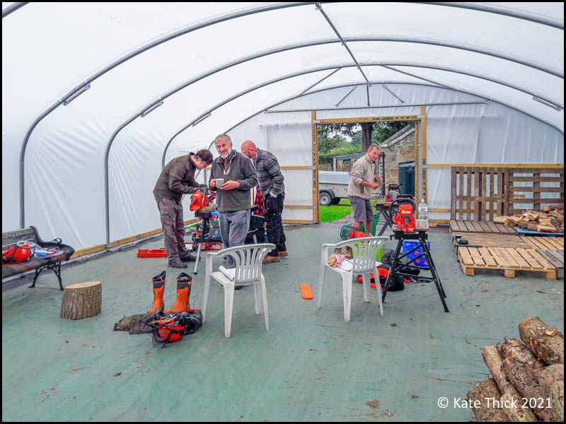Photo of four men working inside poly tunnel